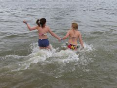 Two women run into the water together.