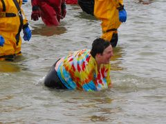 A woman in a tie-dye shirt is on her hands and knees in the water.