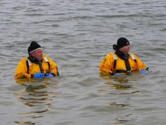 Two men in yellow drysuits stand in the water waiting to come to anyone's assistance if necessary.
