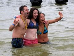 A group of three is all smiles as they pose in the water.