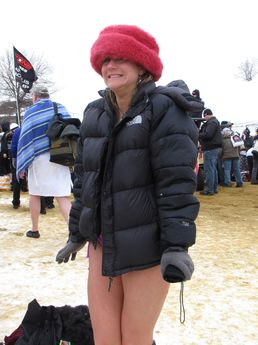 A woman stands on the beach in a heavy coat, hat, and gloves after taking the plunge.