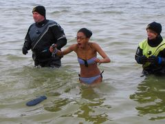 A woman reacts to the cold water.