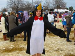 A woman is all smiles, ready to take the plunge while wearing a penguin costume.