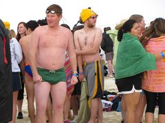 A group of people prepares for the second plunge. The gentleman in the green suit seems particularly cold while waiting to take the plunge.