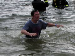 A man reacts to being in the ice cold water.