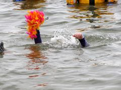 A woman submerges, holding her wig above the water.