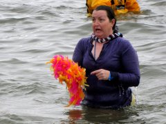 The woman holding her wig emerges from the water.