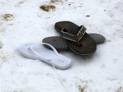 Three abandoned flip-flops on the beach.