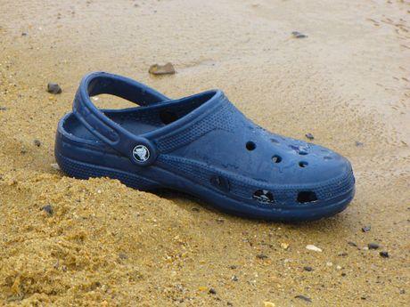 """A """"Crocs"""" shoe sits abandoned on the beach."""