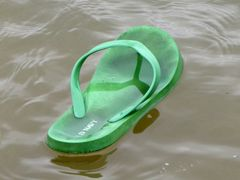 A green flip-flop floats in the water during the first plunge.