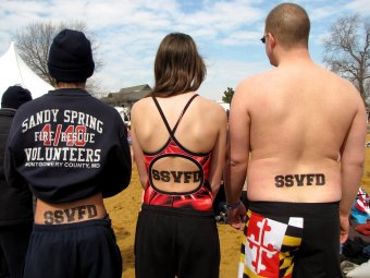 Three members of the Sandy Spring Volunteer Fire Department show off their temporary back tattoo, consisting of the fire department's initials, SSVFD.