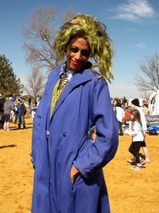 """A woman dressed as the Joker from the Batman franchise poses for the camera, having a mixed level of success in making a proper """"Joker"""" face."""