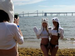 Two women wearing polar bear hats with paws pose for a third person for a photo in front of the water.
