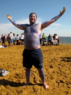 A man, having painted his body blue to show Navy pride, poses for the camera prior to taking the plunge.