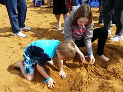 A boy and girl play in the sand on the beach.