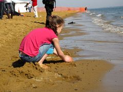 A young girl plays in the sand on the beach.