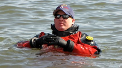 One of the support divers in a drysuit floats in the water, awaiting the start of the third and final plunge of the day.