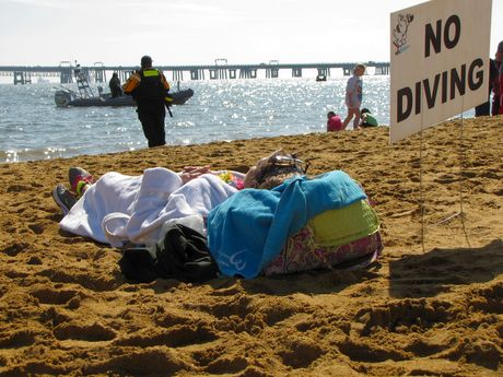 A woman takes a rest on the beach between the second and third plunges.