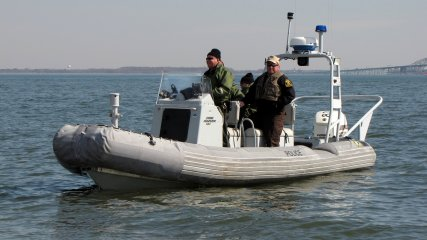 A Maryland Natural Resources Police boat floats on the water just offshore.