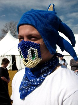 A man shows off his Sonic the Hedgehog costume, consisting of a Sonic-style hat, and a beaded face mask featuring Sonic's face.