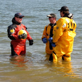 Three of the support divers, wearing drysuits, hold a conversation while standing in the water.