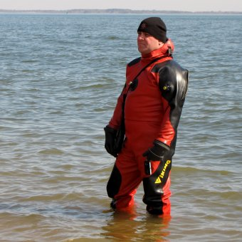 One of the support divers in a drysuit stands in the water, awaiting the third and final plunge of the day.