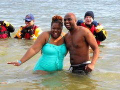 A couple poses for photos while standing in the water during the third and final plunge of the day.