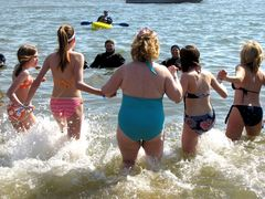 Five women go in the water together during the second plunge of the day.