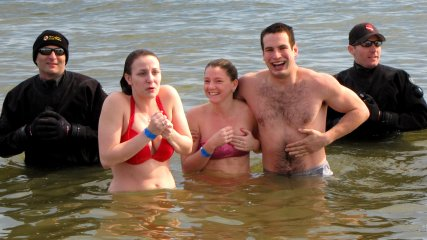 A man and two women pose for photos with the support divers.