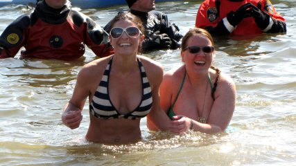 Two women in bikinis and sunglasses take the plunge.