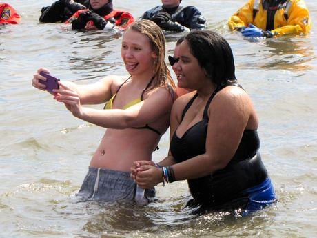 Three women take a selfie in the water.