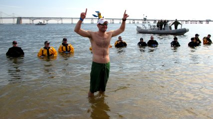 A man poses for photos before leaving the water during the third and final plunge of the day.