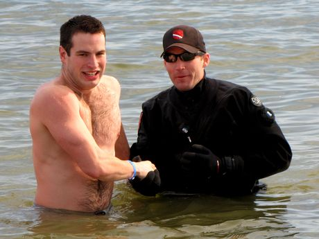 A man poses for a photo of himself shaking hands with the support divers during the third and final plunge of the day.