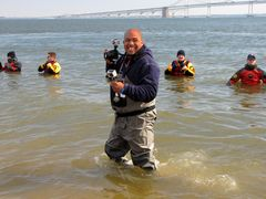 A photographer wearing waders takes photos from the water.