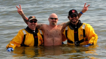A man poses for a photo with the support divers.