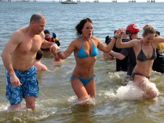 A man and two women take the plunge during the third and final plunge of the day.
