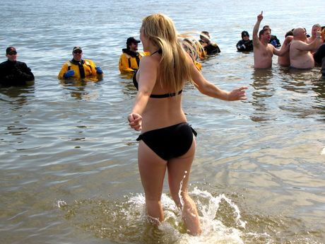 A woman wearing a bikini runs into the water during the third and final plunge of the day.