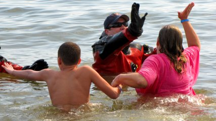 A woman gives a high five to one of the support divers during her plunge.