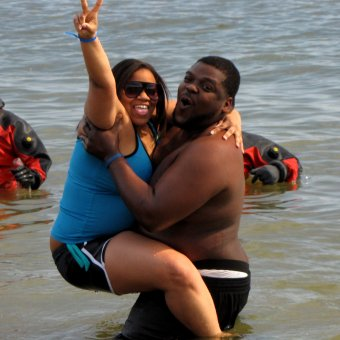 A woman poses for a photo while hanging onto a male companion in the water during the third and final plunge of the day.