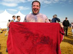 A man, having painted his body blue to show Navy pride earlier in the day, shows off some of the blue paint that had come off onto his towel following his completion of the plunge.