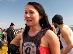 A woman who had previously made a nervous face prior to plunging, smiles following her successful completion of the plunge.