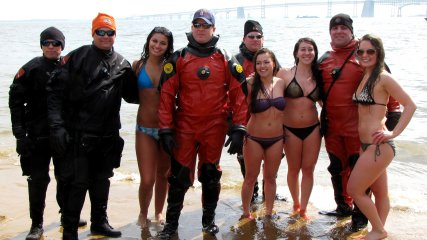Several women in bikinis pose with the support divers in drysuits.