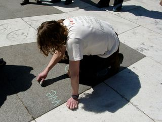 This particular protester doodled his message onto the sidewalk using a piece of green chalk.