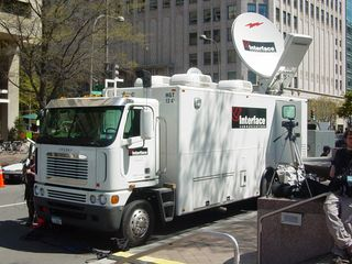The news media was out in force, as to be expected. Along the perimeter, a communications truck has all kinds of equipment including a big satellite dish, and among the crowds, we found an NBC cameraman shooting video footage.