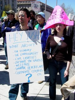 A number of more pressing issues are at hand, as evidenced by the sign held by the gentleman at left. Additionally, he has a peace sign painted on his forehead. The woman next to him has an oversized hat, stating that regime change begins at home, implying that Bush should resign.