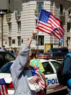 On the outer perimeter, a woman hands out American flags.