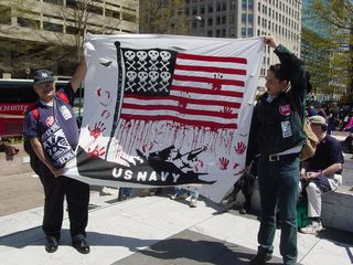 These two demonstrators portray the Navy as the ones with blood on their hands, with the flag's stars being replaced with skull-and-crossbones images.