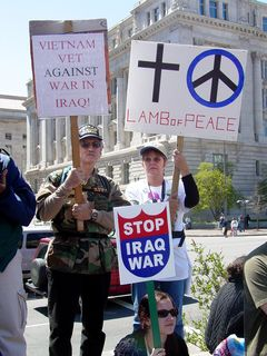 """A Vietnam veteran protests the Iraq war, along with a companion. Also note the """"Stop Iraq War"""" sign being held by the protester in front of them."""