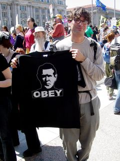 This gentleman holds up a black shirt showing Bush with the single command: OBEY.