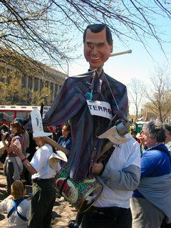 Near the west end of Freedom Plaza, this person holds an effigy of George Bush and beats a drum.